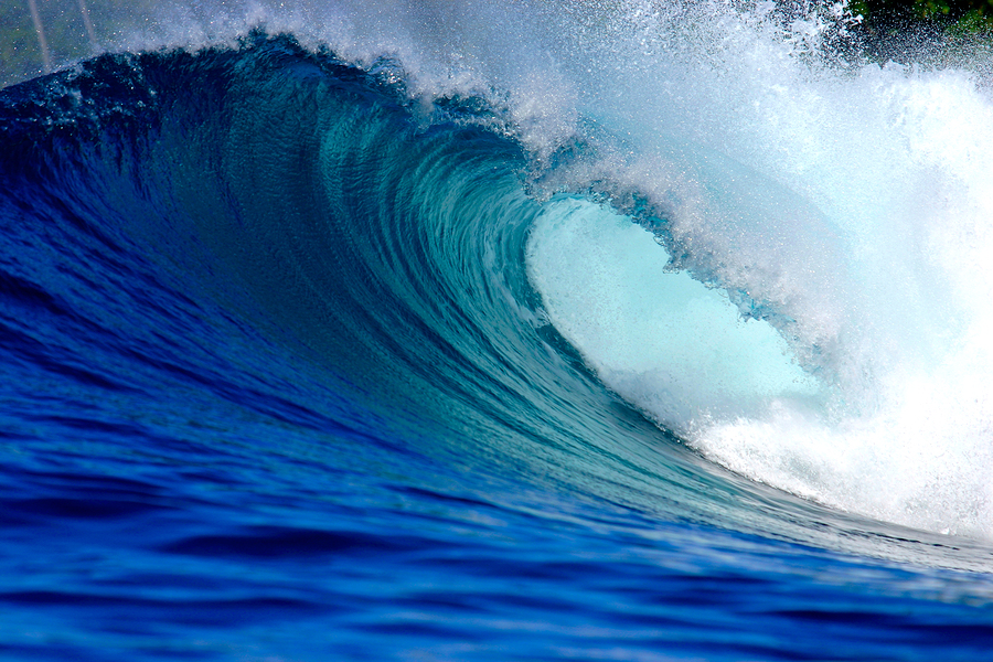 Blue surfing wave breaking on tropical island reef